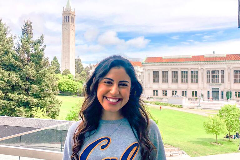 smiling student against the backdrop of the Campanile