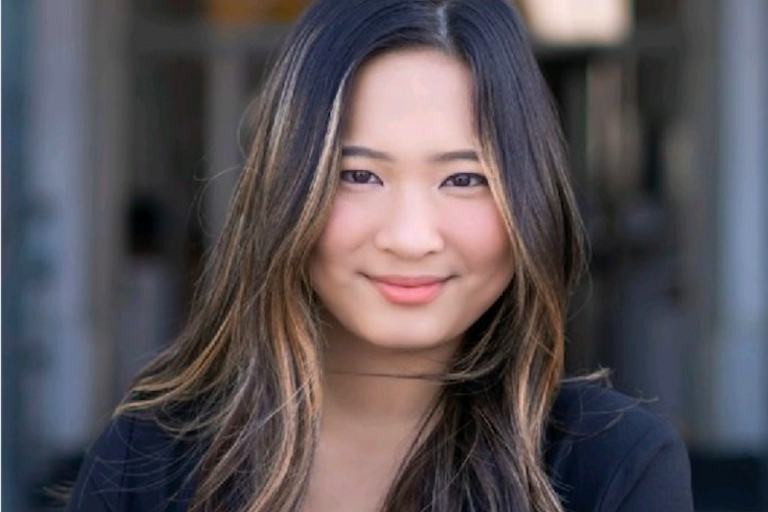 Photo of Nicole smiling and looking at the camera in formal attire