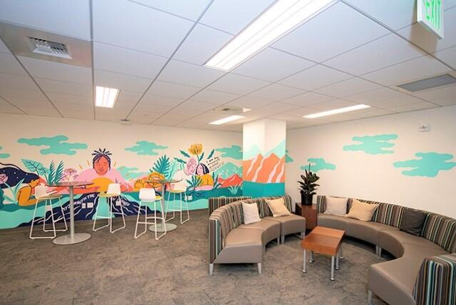 empty Basic Needs Center with colorful mural and sofas