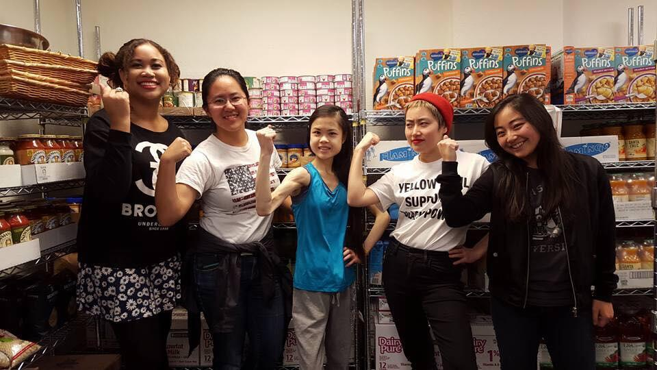 pantry volunteers jokingly flexing in front of food shelves