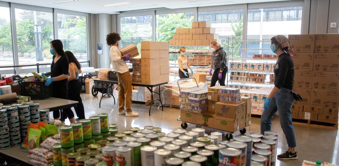 masked up food pantry volunteers unpacking boxes of food