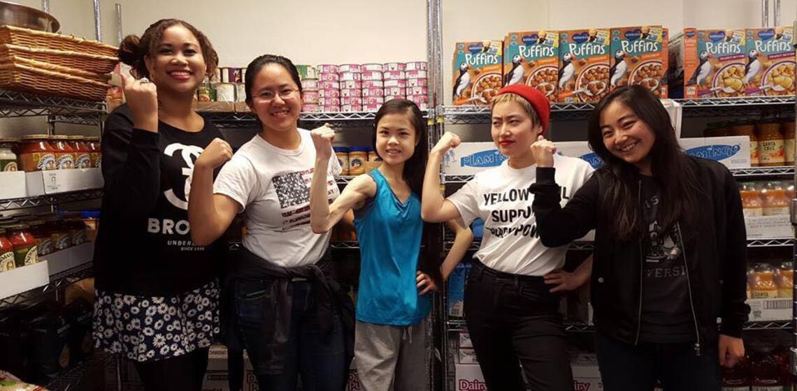 pantry volunteers jokingly flexing in front of food shelves