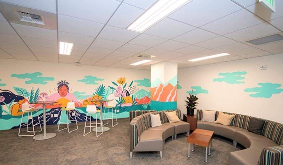 basic needs center lounge with chairs and mural