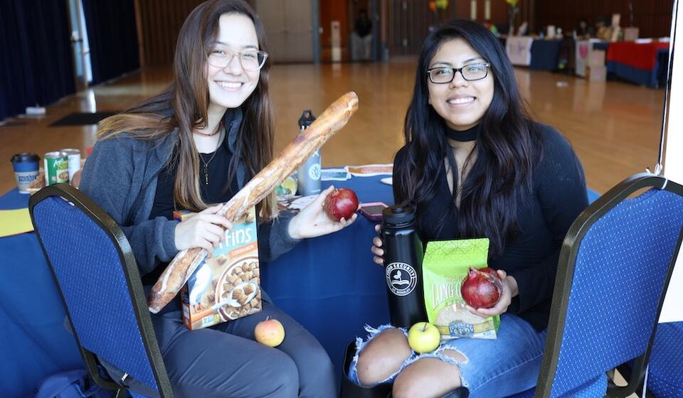 Two students sitting and smiling while holding bread and fruits